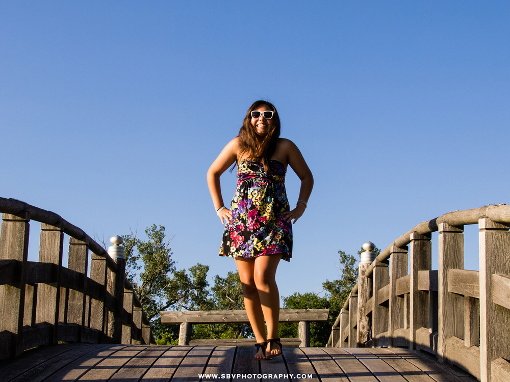 A young girl walks across the bridge at the Marquette Park Pavilion for her senior picture.
