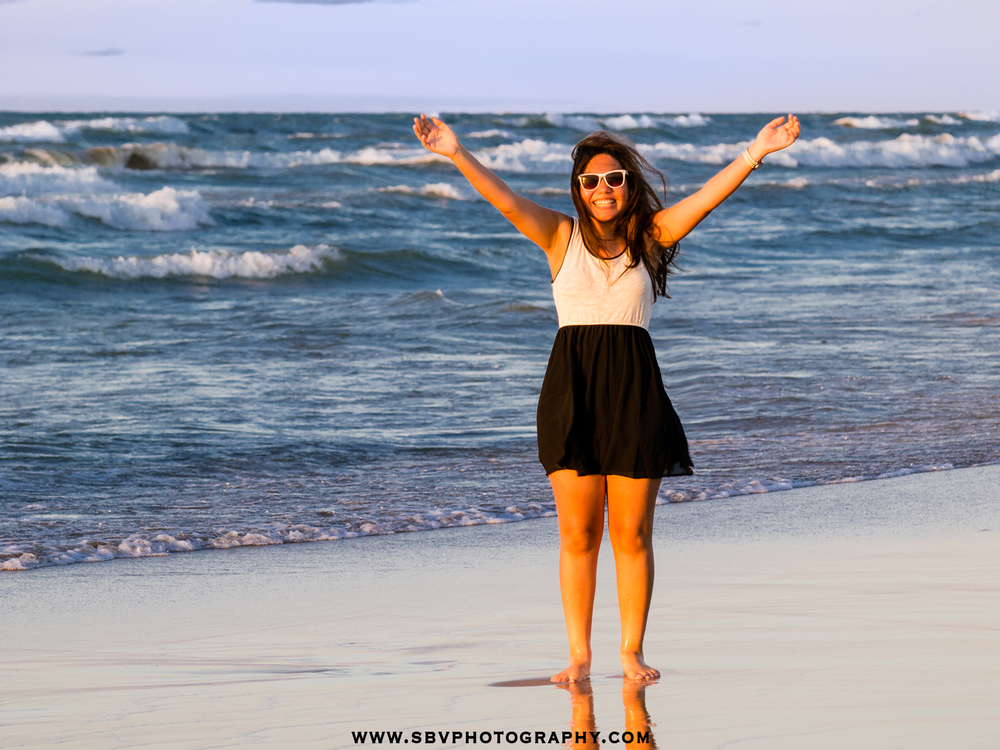 A high school senior girl celebrates as waves from Lake Michigan wash around her feet.