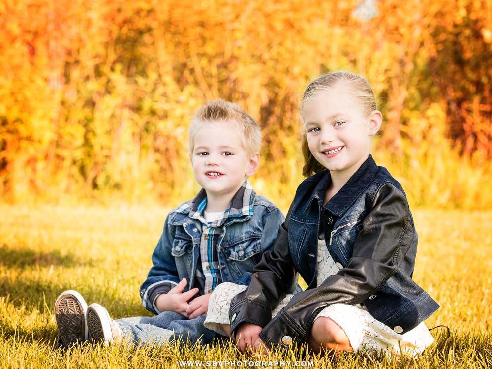 Brother and sister pose for a Fall portrait while sitting in the grass together in a Griffith park with red tinged leaves.