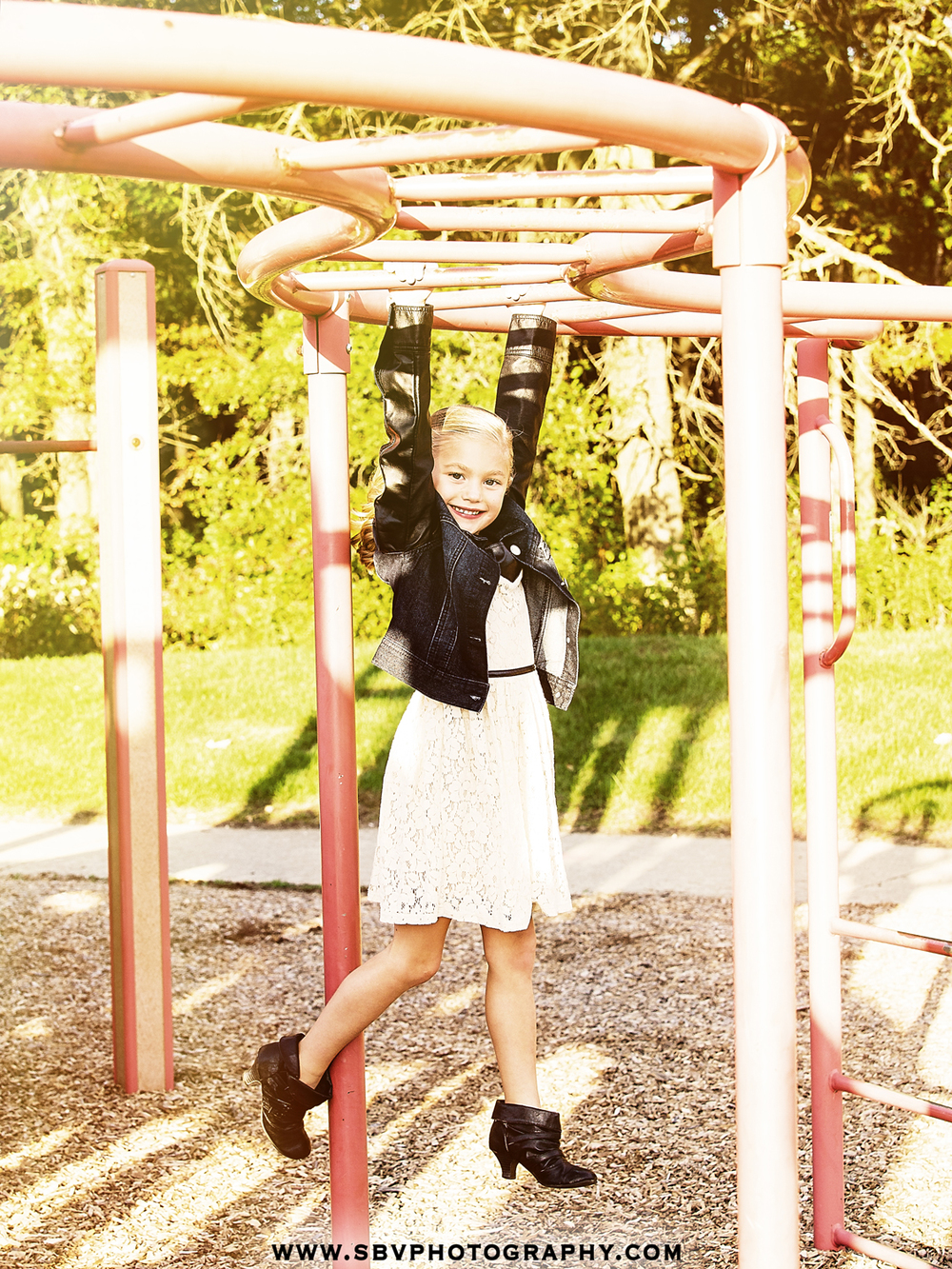 Little girl swings from the trapeze bars at Oak Ridge Prairie playground.