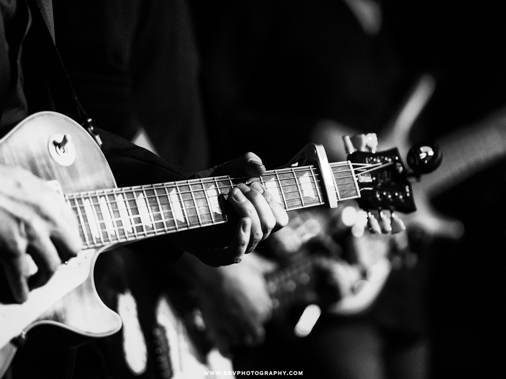 Close up photo of a guitar player's hands on the neck of a Les Paul.