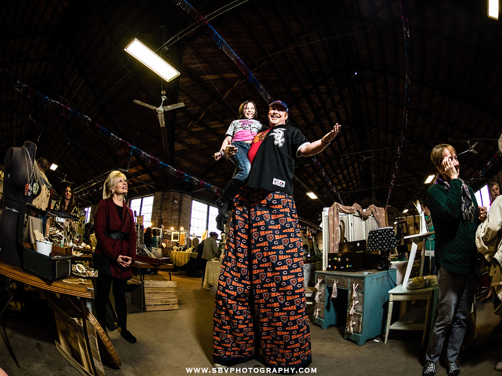A man on stilts raises a child for a bird's eye view of the indoor festival.