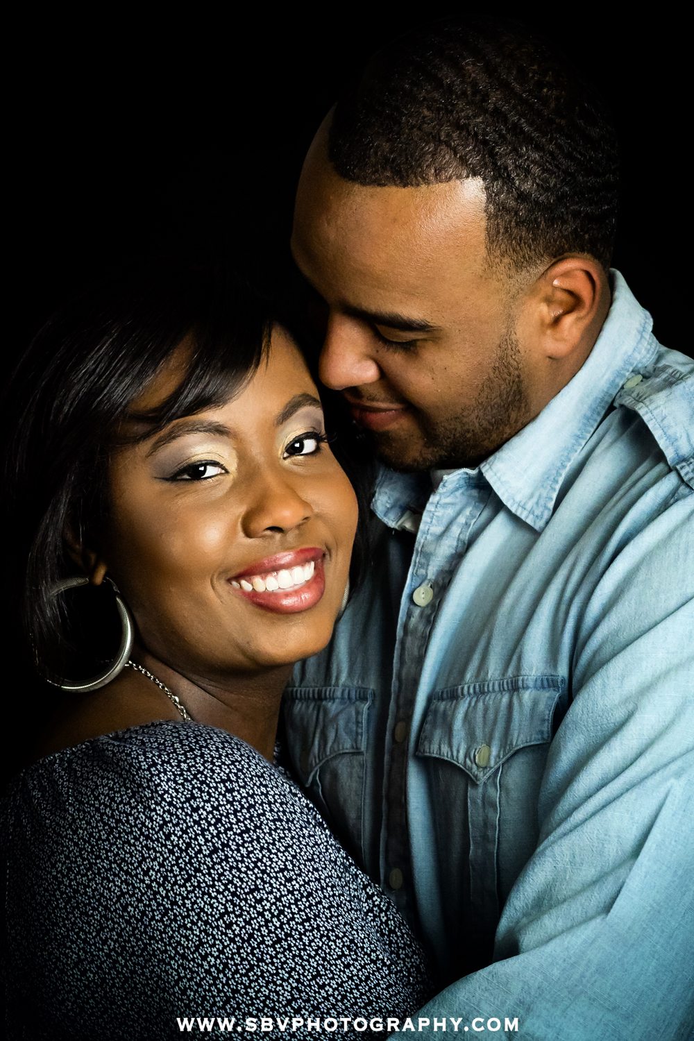 A couple in love embraces during their studio portrait session.