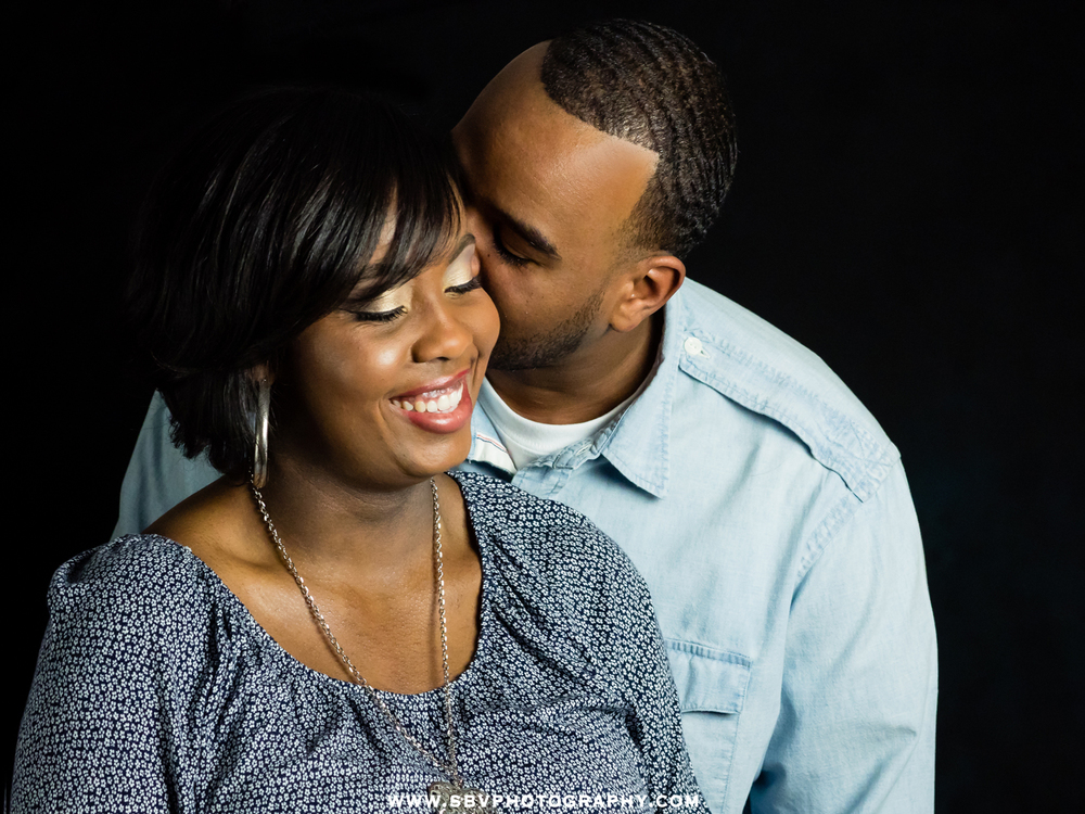 A man whispers into his fiancés ear during their studio portrait session.