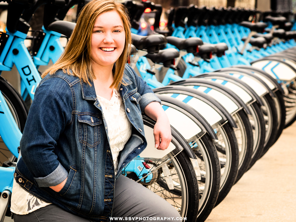 A high school senior leans against a row of blue bicycles on Michigan Avenue in downtown Chicago.