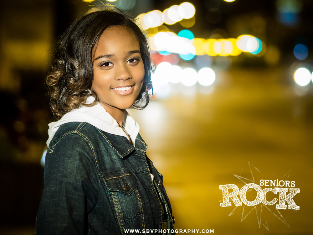 A high school senior girl on Michigan Avenue at night.
