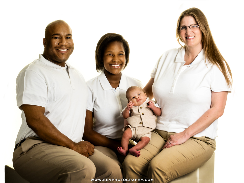 A family celebrates their new arrival with a studio family portrait.