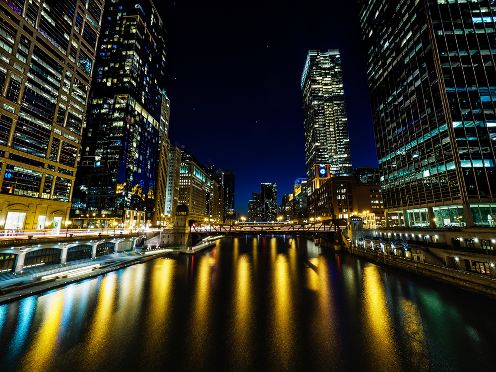 Building lights reflect off of the Chicago River at night.