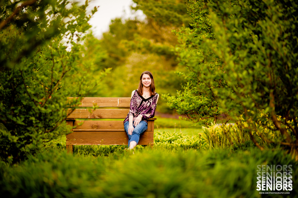 Senior girl sits on a bench in one of the beautiful gardens of Taltree Arboretum.