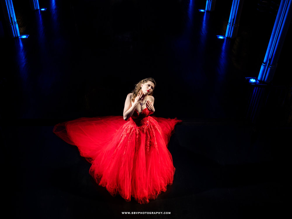 Alex W. on stage in the Scarlett Obsession dress with blue uplighting.
