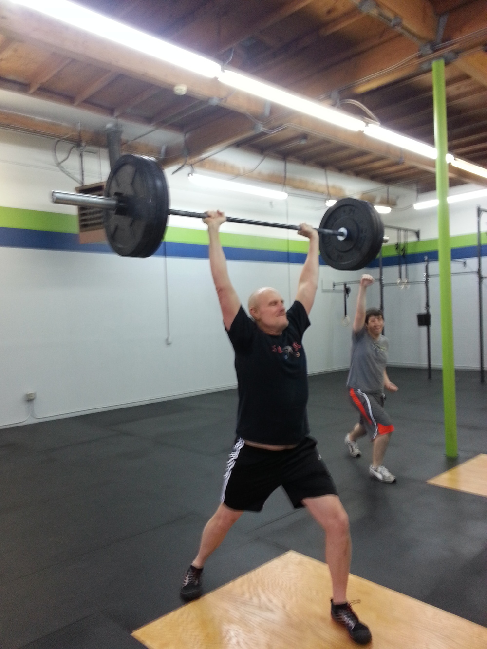 Steve hitting a PR Jerk, and Phil celebrating in the background.