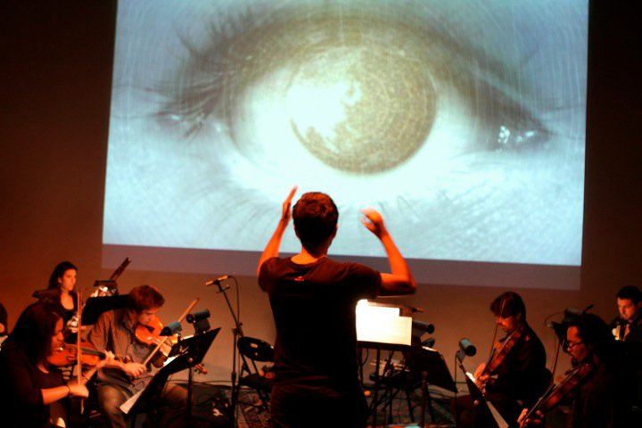 William D. Caballero conducting a 20-piece ensemble with projected graphics.