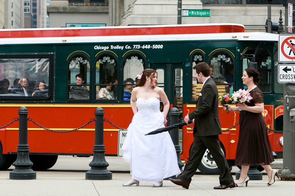 Wedding couple walks on Michigan Ave. as trolley passes by.
