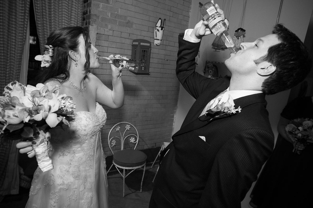 Bride & groom celebrate by drinking Coronas during their Catalyst Ranch wedding.
