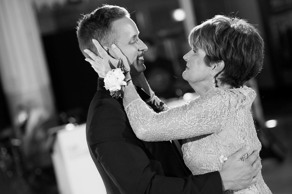 A mother embraces her son during his wedding reception at the Shedd Aquarium.