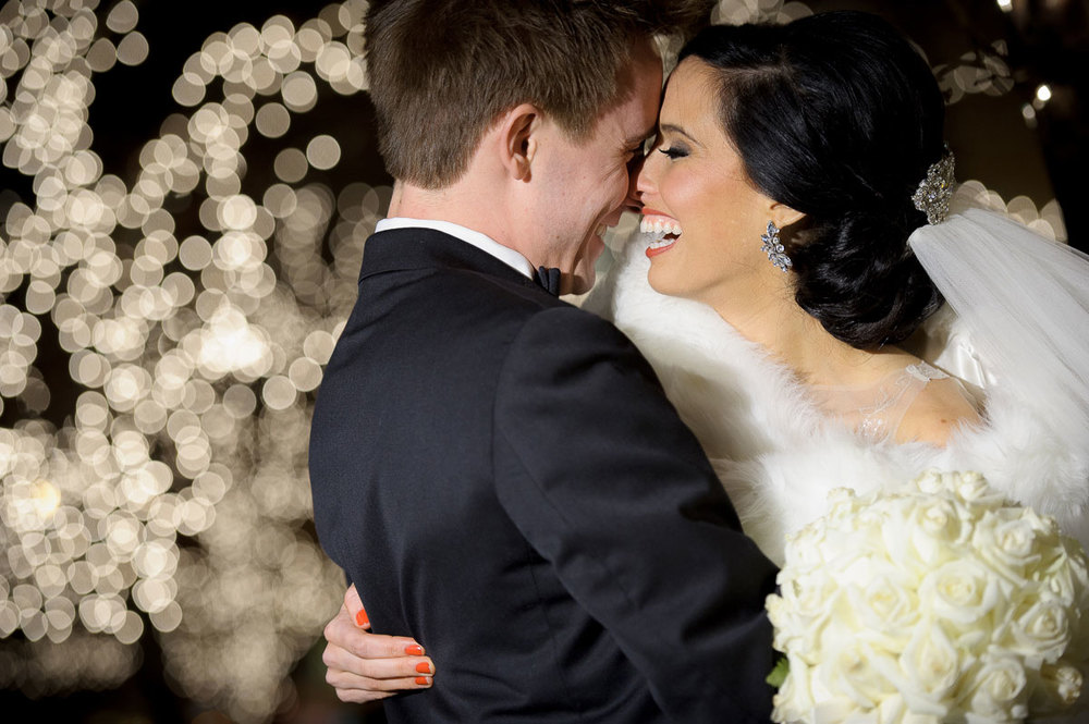 Bride & groom share a laugh during this Christmas lights wedding portrait in Chicago.