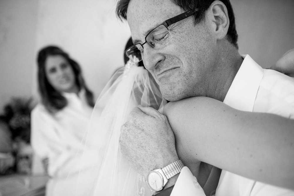 Photojournalistic wedding day moment of the father-of-the-bride embracing her daughter in Chicago.