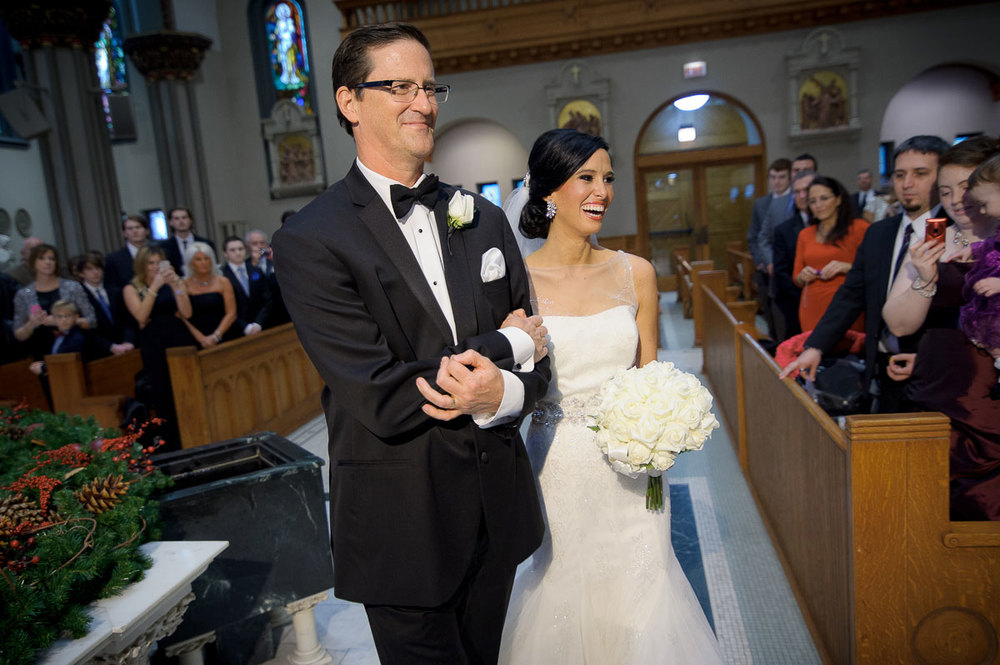The bride is escorted down the aisle during her St. Vincent De Paul Chicago wedding.