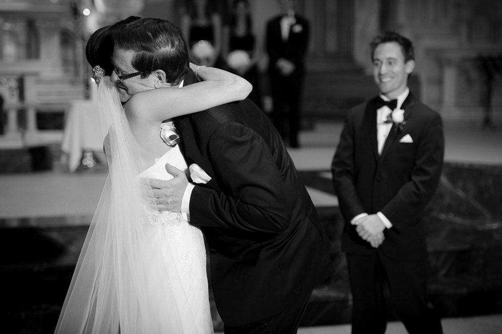 Father-of-the-bride embraces his daughterduring her St. Vincent De Paul Chicago wedding.