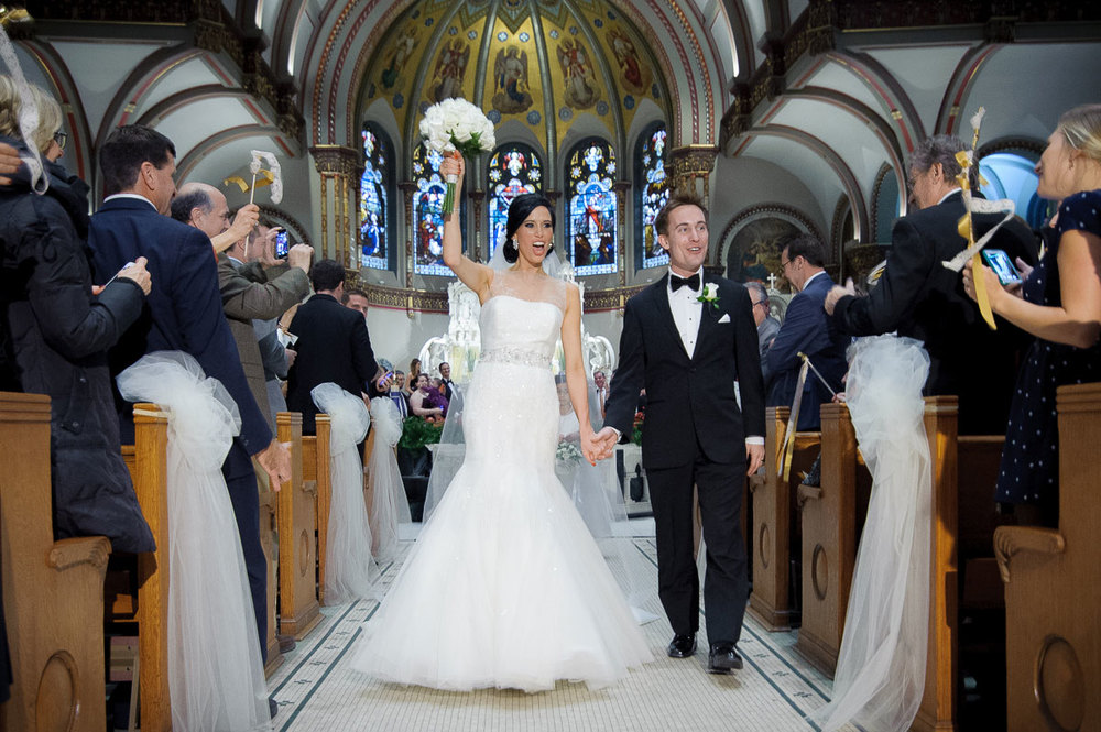 Bride & groom walk down the aisle during theirSt. Vincent De Paul Chicago wedding.