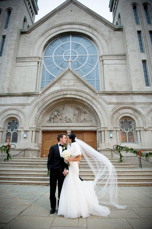 Bride & groom kiss outsideSt. Vincent De Paul Chicago.