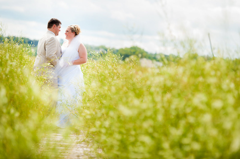 Bride & groom embrace amongst the reeds along Lake Michigan during their Blue Harbor Resort wedding.