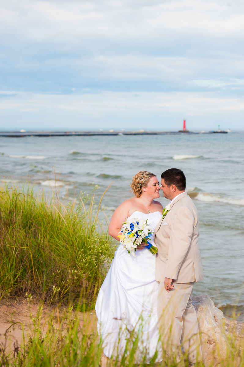 The couple embraces on the shores of Lake Michigan after their wedding ceremony at Blue Harbor Resort.