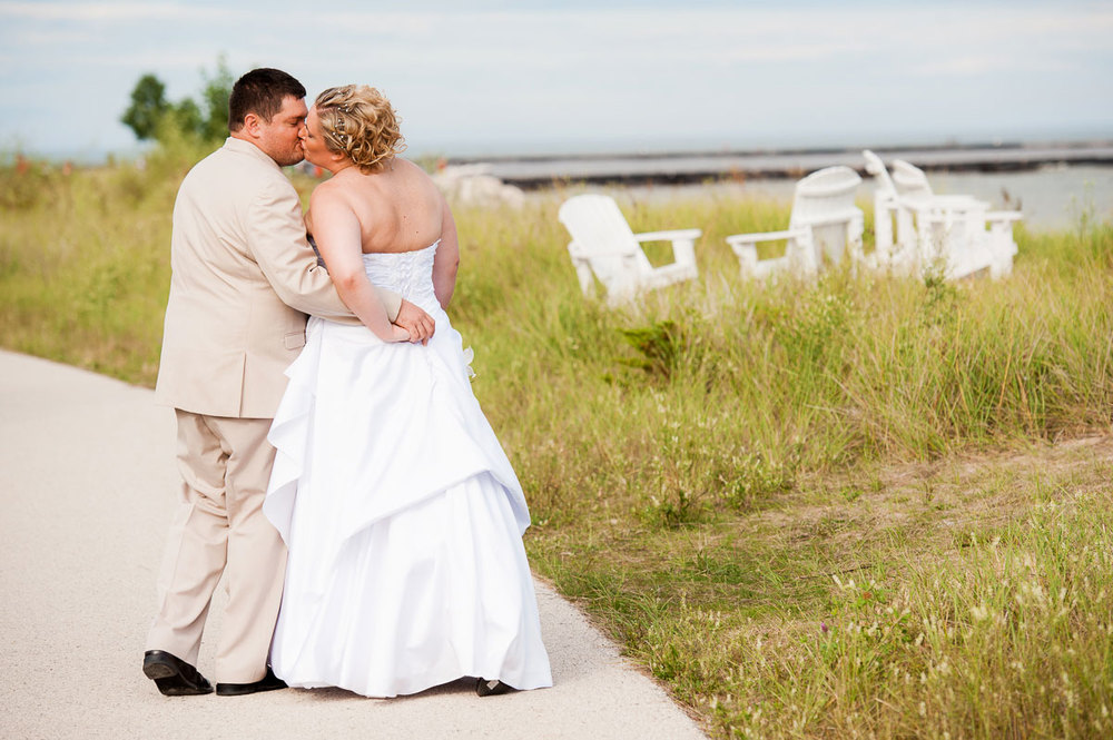 Bride & groom share a kiss while walking along the beach at Blue Harbor Resort.