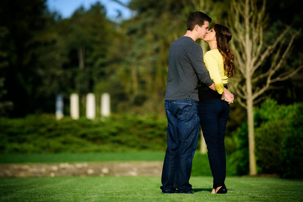 A couple kisses during their engagement session at the Morton Arboretum in Lisle, IL.
