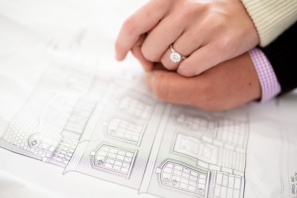 Couple looks at the blue prints of their Wicker Park home during their Chicago engagement session.