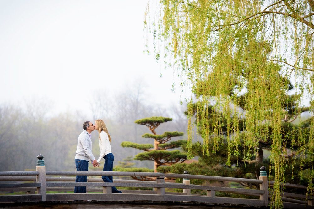 Couple kisses on a bridge at the Chicago Botanic Gardens during their engagement session.