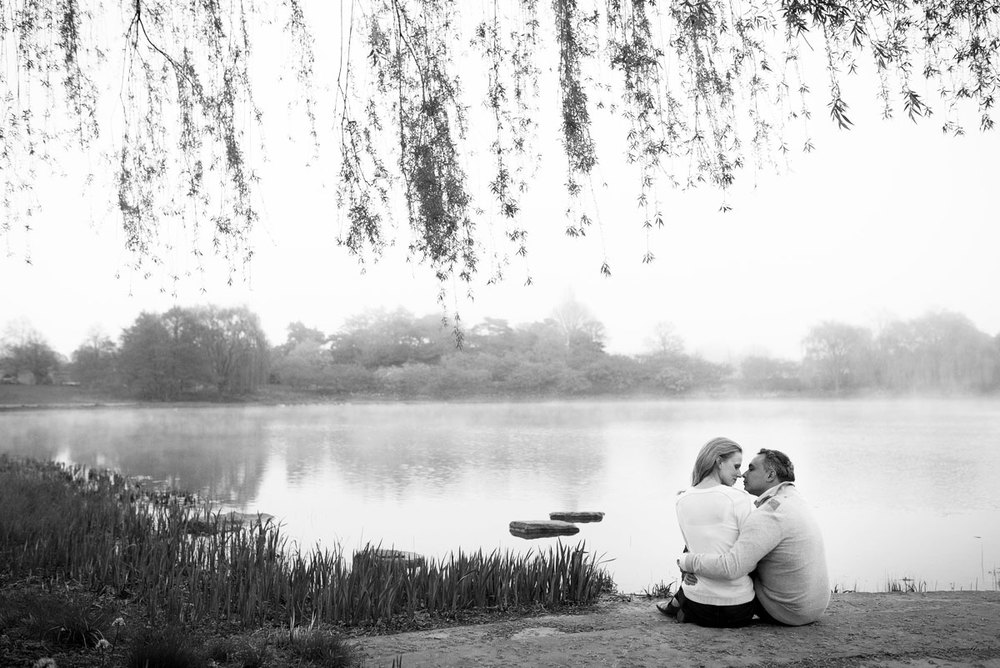 The couple embraces near a foggy lake during their engagement session at the Chicago Botanic Gardens.