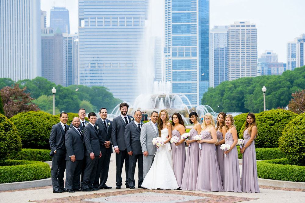 Bridal party photo at the Tiffany Gardens with Buckingham Fountain in the background.