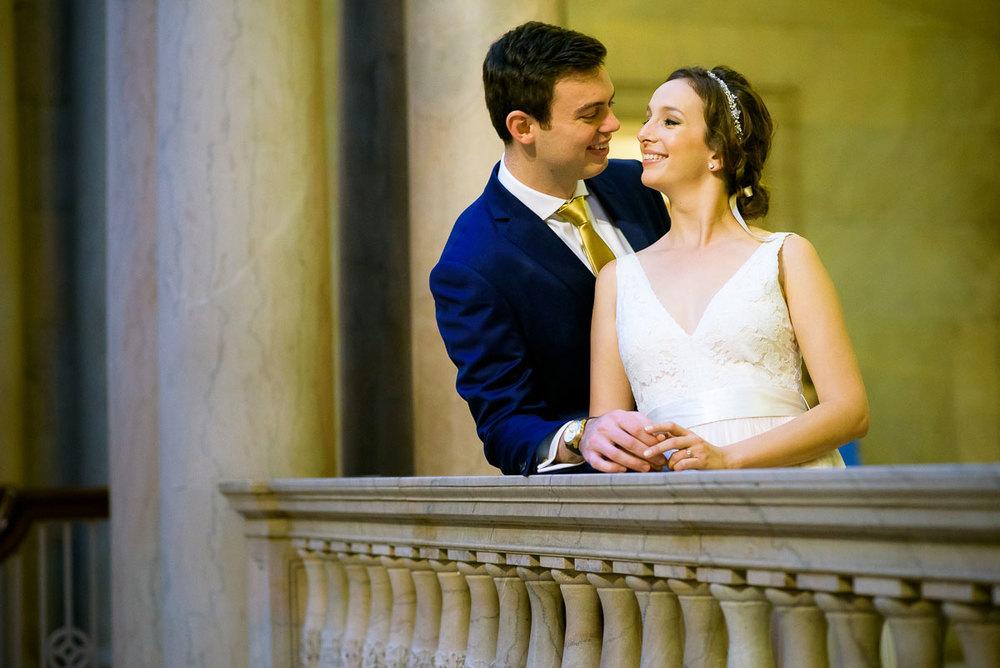 Bride & groom embrace in the atrium of the Art Institute of Chicago.