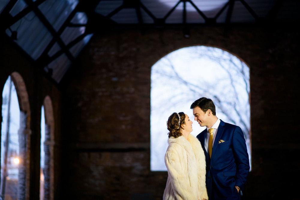 Bride & groom embrace in the sculpture garden during their Bridgeport Arts Center wedding.
