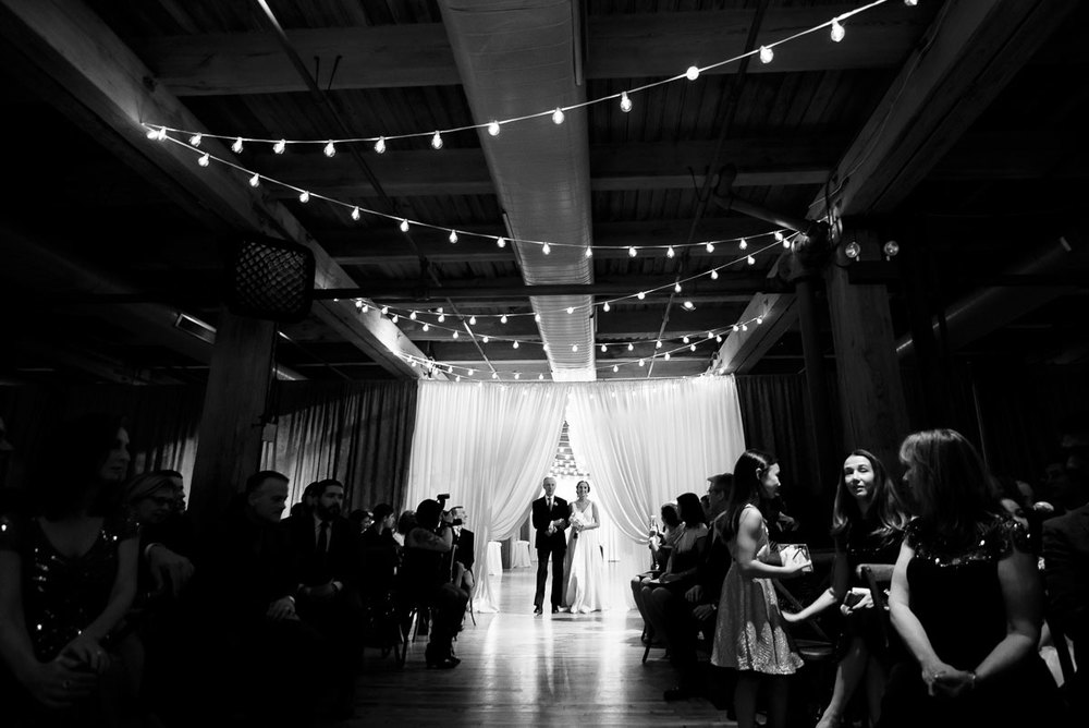 The bride walks down the aisle during her wedding at the Bridgeport Arts Center.