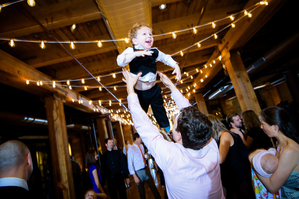 One of the ring bearers is tossed in the air during a Bridgeport Arts Center wedding.