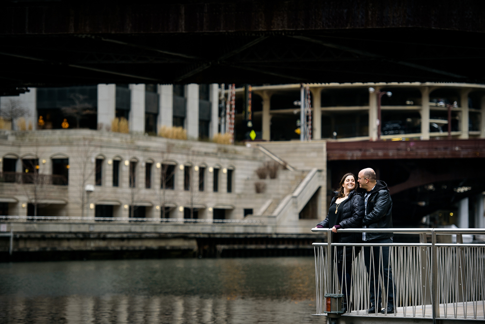 A couple stands together under the Clark Street Bridge along the Riverwalk during their Chicago engagement session.