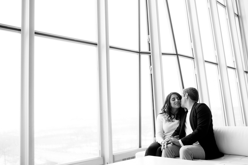 The couple kisses near the windows at Venue Six10 during their Chicago engagement session.