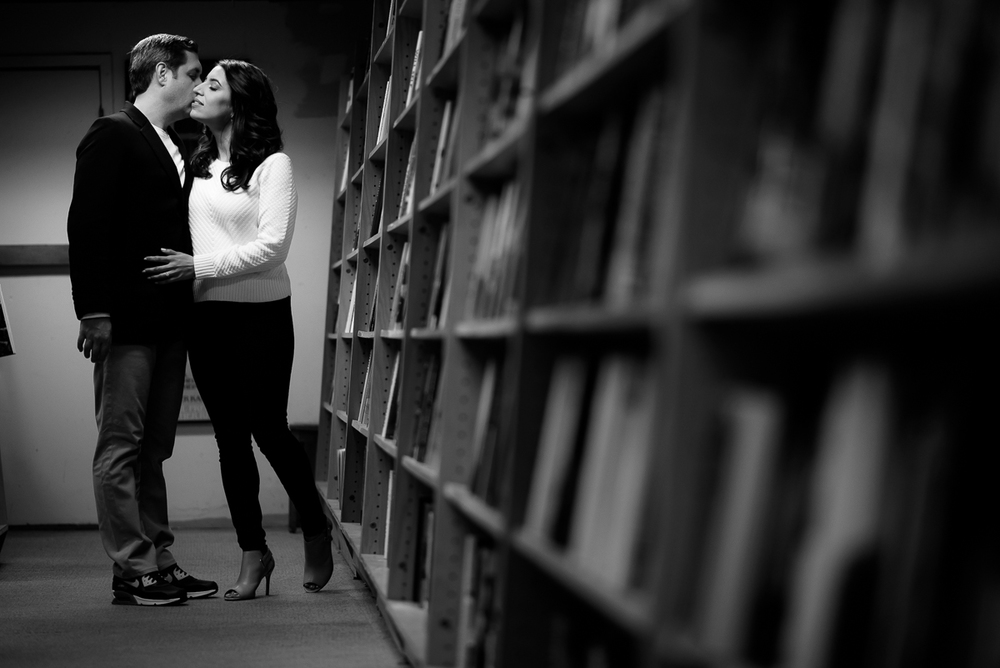 The couple embraces among the books during their engagement session. at Afterwords in Chicago.