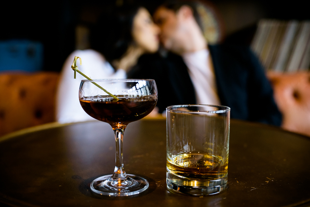 The couple shares a cocktail and a kiss during their Chicago engagement session at The Betty.