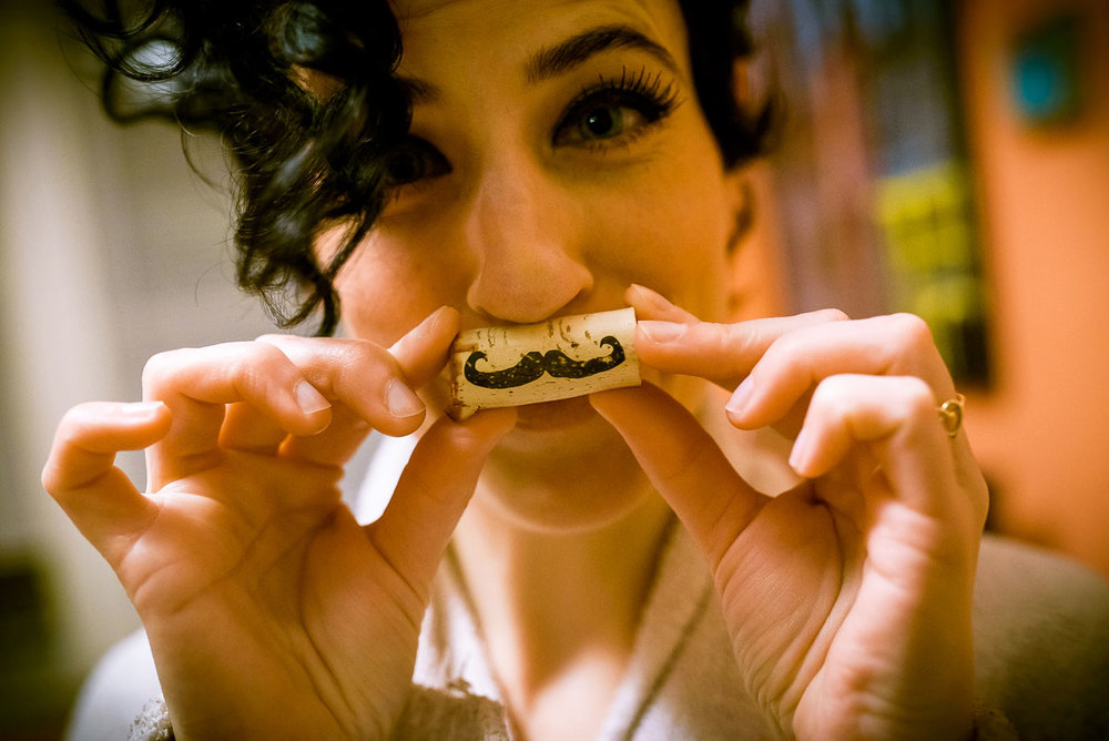 Bride being goofy while a wine cork while getting ready on her wedding day.