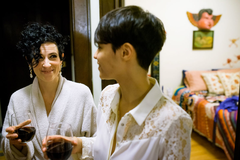 The couple shares a moment over wine while getting ready at their apartment on their wedding day.