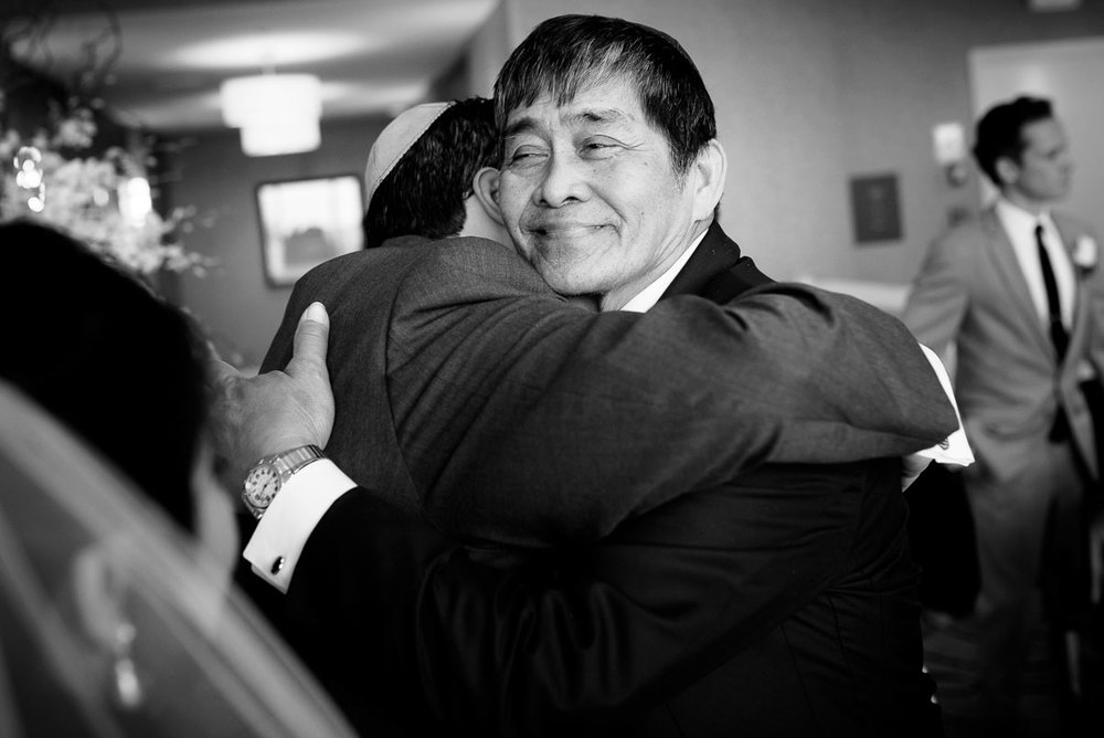 Father-of-the-bride hugs the groom after the wedding ceremony at the DoubleTree Skokie.