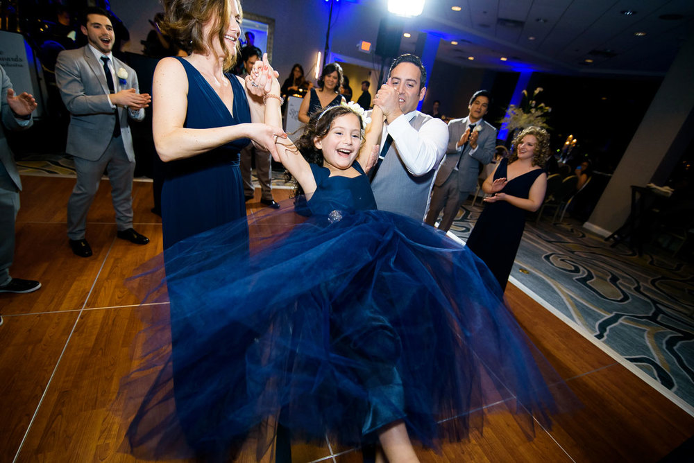 The flower girl is twirled around on the dance floor at a DoubleTree Skokie Wedding.