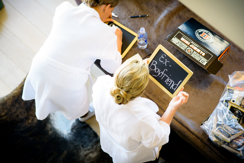 Bridesmaids make signs of how they know the bride while getting ready at the Thompson Chicago.