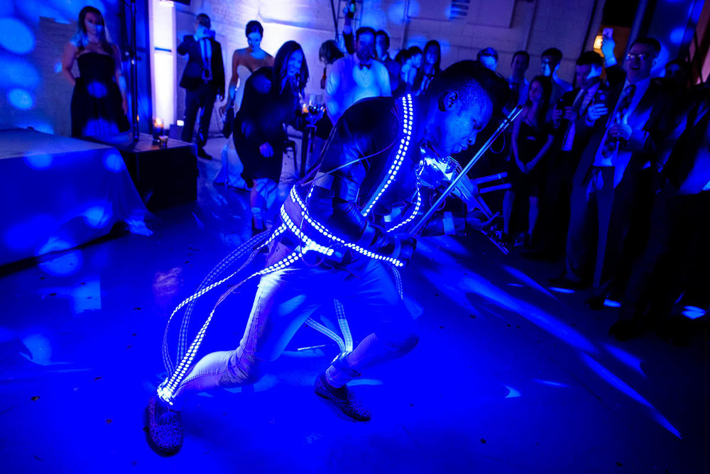 DJ/Violinist Timothee Lovelock wears and LED lighted suit during a wedding reception at Moonlight Studios Chicago.