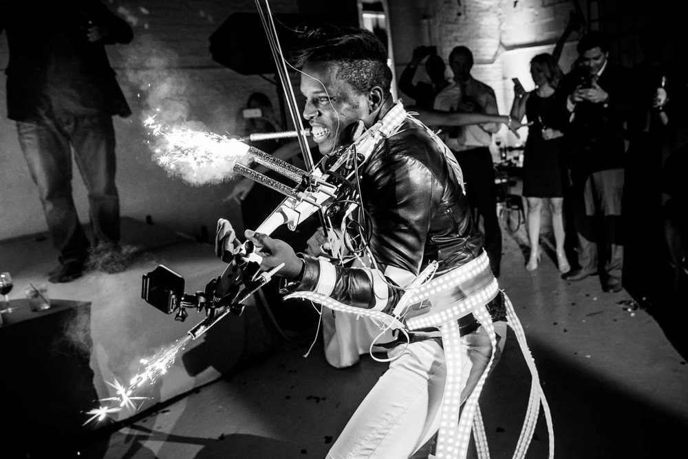 DJ/Violinist Timothee Lovelock lights sparklers on his violin during a wedding reception at Moonlight Studios Chicago.