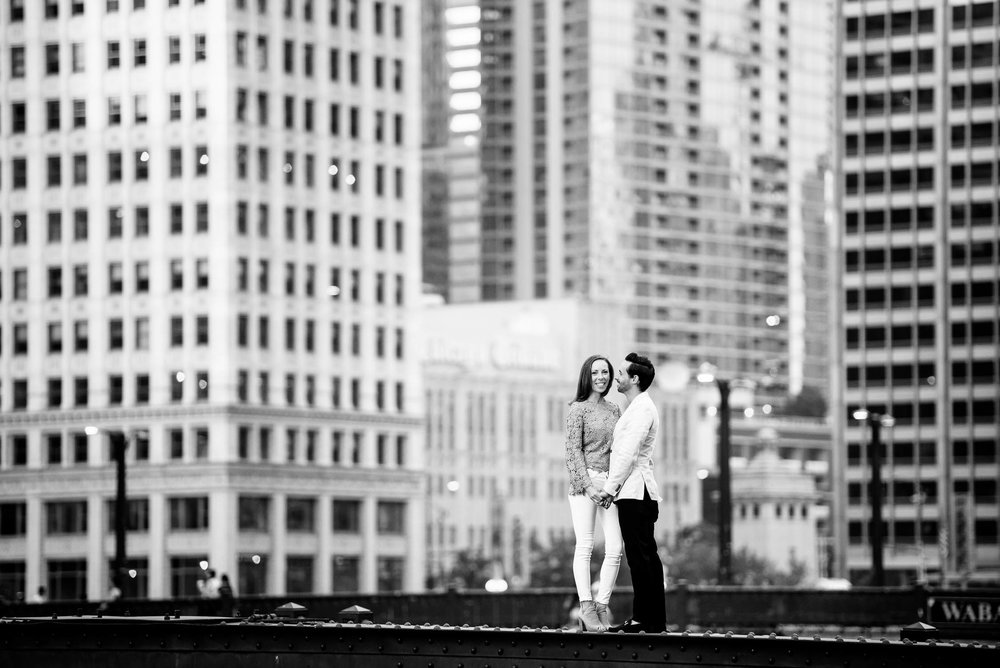 Couple stands on the State St. Bridge during the Chicago Riverwalk engagement session.