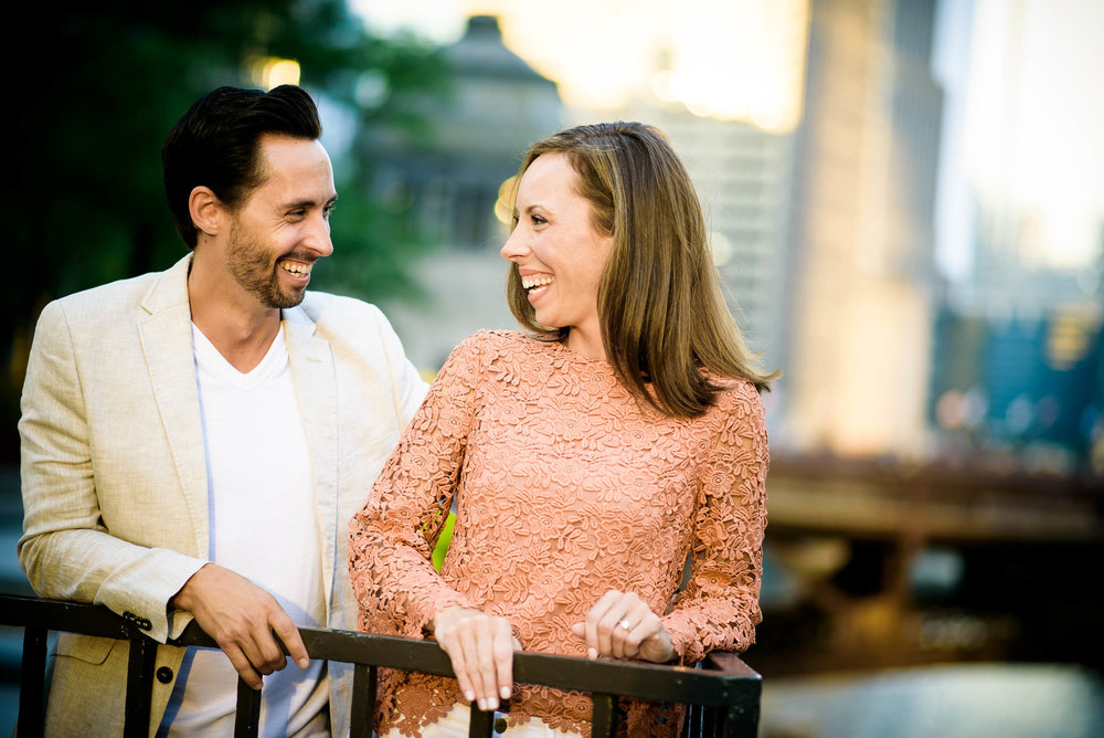 Couple share a laugh together during their Chicago engagement session on the river.
